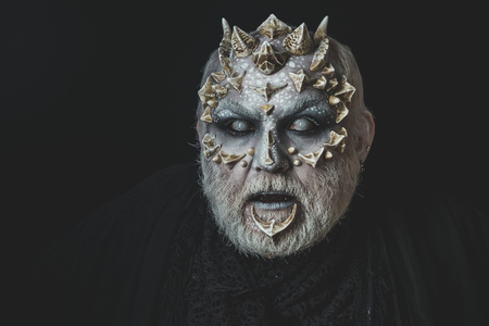 Monster with thorns and horns. Man with blind eyes. Demon head isolated on black. Horror and fantasy concept. Alien face with dragon skin and grey beard.
