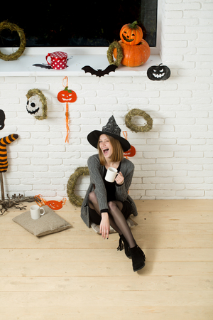 Halloween girl sitting on wooden floor. Woman in witch hat winking with cups. Coffee or tea break. Happy holiday celebration concept. Pumpkins, wreaths, mummy symbols and decorations on brick wall.