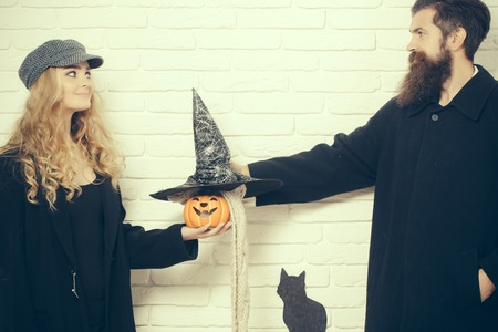Halloween couple and black cat symbol on brick wall. Woman holding pumpkin and man with witch hat. Autumn holiday celebration concept. Evil spell and magic. Trick or treat.