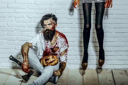 Halloween female legs in black pantyhose hanging on white wall. Man sitting with bloody pumpkin and axe on wooden floor. Bearded hipster with red blood. Crime and violence. Halloween holiday concept