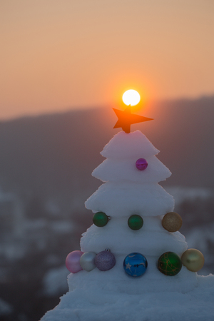 Snow sculpture with red star on natural background. Decorations and ornaments. Winter holidays concept. xmas and new year celebration. Christmas tree with baubles on sunset sky.