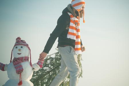 Hipster slepende Kerstmis boom op besneeuwde winter weg. Kerel en sneeuwbeeld die hoeden en sjaals dragen. Vakantie feest concept. Kerstmis en Nieuwjaar. Mens en sneeuwman die op blauwe hemel lopen.