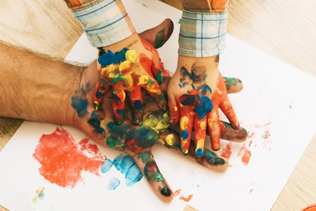 Fathers day, family love and care. Arts and crafts. Handprint painting concept. Hands and fingers drawing with multicolor paints on white paper. Imagination, creativity and freedom. Stock Photo