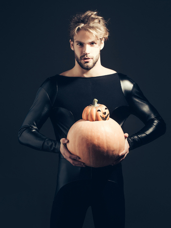 Halloween autumn and harvest season. Man holding two pumpkins on dark background. Macho in black costume with jack o lantern. Holidays celebration concept. Trick or treat. Фото со стока