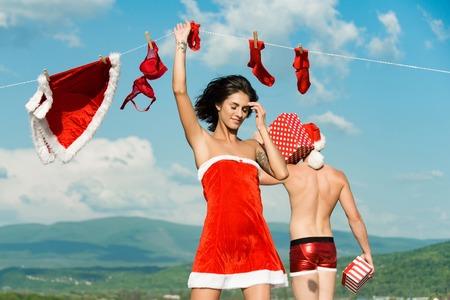 celebration: christmas couple in love og woman and santa man on blue sky
