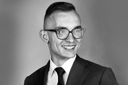 young fashion businessman with nerd glasses on smiling face and stylish hairdo in jacket with tie on studio background Stock Photo