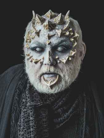 man or scared monster with thorns on face with futuristic makeup as alien with beard and lens in eyes on black background Stock Photo