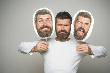 Guy or bearded man on grey background. Man with long beard and mustache. Feeling and emotions. Hipster with winking, happy and serious face hold portrait nameplate. Barber fashion and beauty.