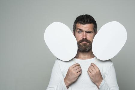 ファッションと美容理容室します。男や背景が灰色のひげを生やした男。長いひげと口ひげを持つ男。感覚や感情。深刻な顔でヒップを保持する紙