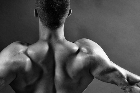 Sexy muscular male back of athlete bodybuilder posing in power with raised hands and bare torso on dark background 版權商用圖片