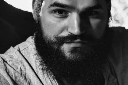 Closeup view portrait of one handsome serious young adult man with long black lush beautiful beard and moustache looking forward indoor on blurred background, horizontal picture 版權商用圖片