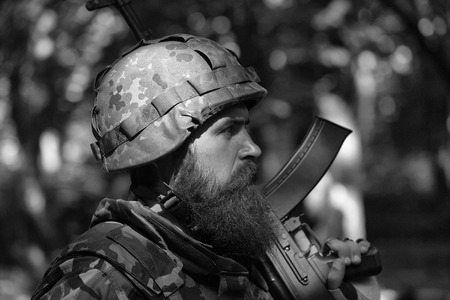Young soldier man with beard on sad face in helmet and military ammunition with rifle on shoulder in profile on forest outdoor