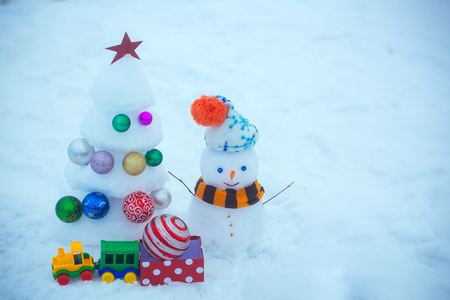 Snowman with smiley face in hat and scarf. xmas and new year. Christmas tree with decorations, toy train and present box. Winter holidays concept. Snow sculptures on blue background, copy space