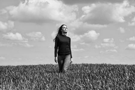젊은 섹시 한 여자 또는 여자 갈색 머리 머리와 검은 얼굴에 예쁜 얼굴 카디 건과 청바지 흐린 푸른 하늘 필드에 녹색 잔디 자연 배경