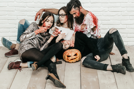 Halloween zombie people of bearded man, long beard, brutal caucasian hipster with moustache hold pumpkin, axe and bloody women with wounds and red blood on white brick wall background