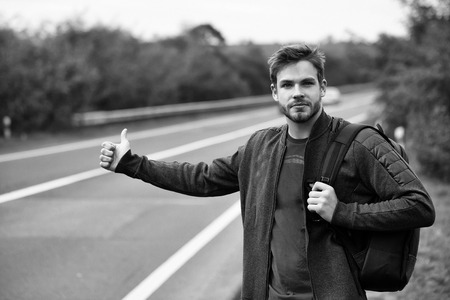 Young man hitchhiking with bearded serious handsome face in black and red casual clothes with bag standing near road way with hand autostop outdoor