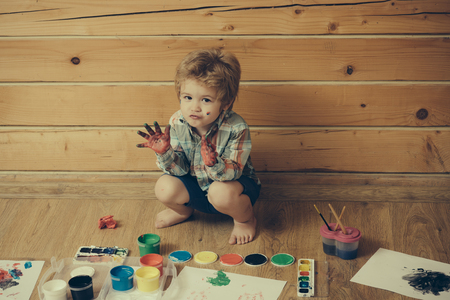 Imagination, creativity and freedom concept. Child with colored hands, gouache paints and drawings. Arts and crafts. Kid learning and playing. Boy painter painting on wooden floor.