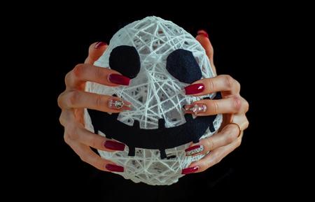 Halloween-brij in vrouwelijke die handen op zwarte achtergrond wordt geïsoleerd. Geest en bovennatuurlijk. Wit gezicht met spookachtige smiley en manicure met edelstenen. Nagelkunst concept. Feestdagen en feestviering.