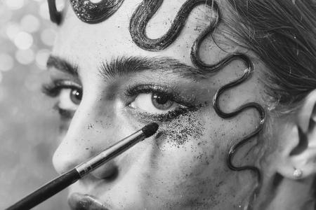Mooi meisje of mode vrouw zetten vakantie, glitter oogschaduw make-up, fonkelend oog make-up, met borstel en schattig, krullend haar lock, kapsel, op jonge gezicht