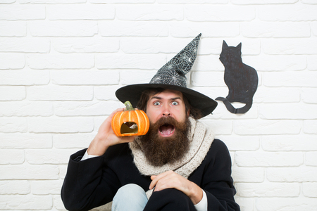 Halloween autumn holidays celebration. Scared hipster with pumpkin and black cat symbol on wall. Man in witch hat sitting on floor. Bad luck concept. Evil spell and magic. Banco de Imagens
