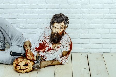 Halloween bearded hipster with red blood splatters. Man lying with axe and pumpkin on wooden floor. Psychopath bleeding in torn tshirt. Halloween holiday concept. Maniac and bloody jack o lantern.