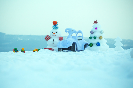 smiley face car: Snowman and toy car on snowy background. Holidays celebration concept. Christmas tree and present box on blue sky. Snow sculpture with smiley face on winter day. xmas and new year. Stock Photo