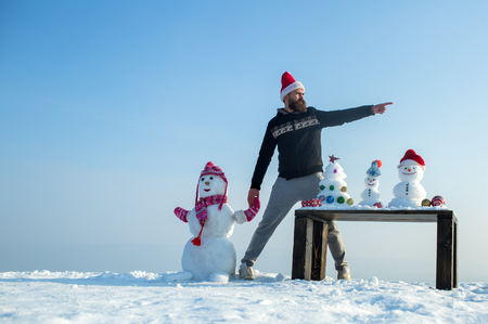 Hipster in red santa hat pointing finger. Man and snowman holding hands on blue sky. Christmas and new year. Snow sculptures and xmas tree on wooden table. Winter fun and holidays celebration concept.
