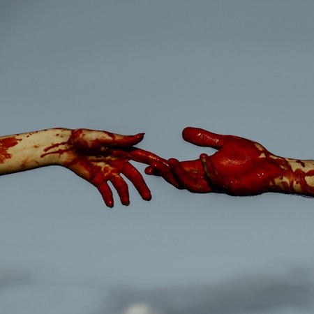 Halloween female and male hands connecting. Two vampires touching fingers on grey sky background. Skin with red blood and bloody wounds. Connection and support. Halloween holiday celebration concept. Stock Photo