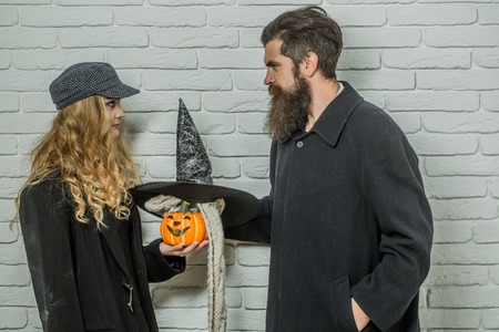Halloween woman holding pumpkin and man with witch hat. Couple and black cat symbol on brick wall. Trick or treat. Autumn holiday celebration concept. Evil spell and magic.