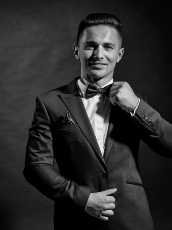 young handsome gentleman with smiling face in fashion black suit white shirt and bow tie in studio