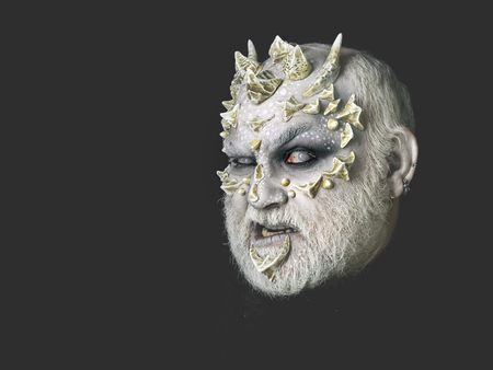 creepy alien: Horror and fantasy concept. Man with dragon skin and grey beard. Monster with sharp thorns and warts on face. Demon head on black background. Alien or reptilian makeup, copy space