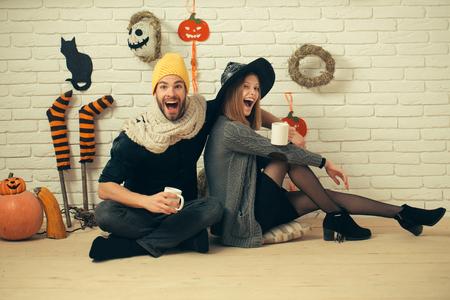 スカーフと黄色のキャップに笑みを浮かべてハロウィーン男。魔女の帽子の「まばたき」の女の子。お祭りでアットホームな雰囲気。幸せな休日の 写真素材
