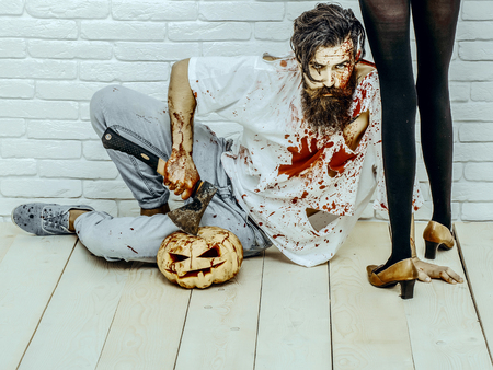 Halloween bearded hipster with red blood splatters. Female legs standing in black pantyhose and shoes. Man sitting with pumpkin and axe on wooden floor. Halloween holiday celebration concept
