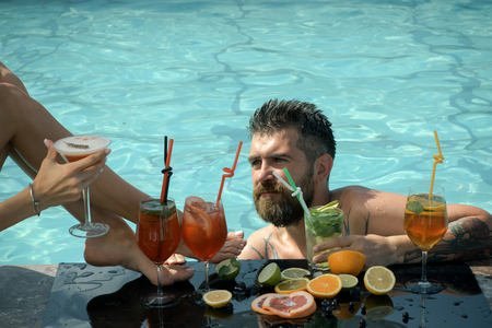 man drinking water: Summer vacation and party. Leg of girl and guy with alcoholic beverage and fruit. Cocktail and bearded man in pool. Man swimming in water pool. Drink, food and relax.