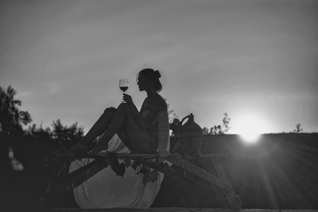 Silhouette of slim girl young woman female model sommelier with wine glass and wicker bottle on nature over beautiful sunset Stock Photo - 87758357