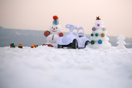 Christmas tree and present box on rosy sky. Holidays celebration concept. Snowman and toy car on snowy background. Snow sculpture with smiley face on winter day. xmas and new year. 版權商用圖片