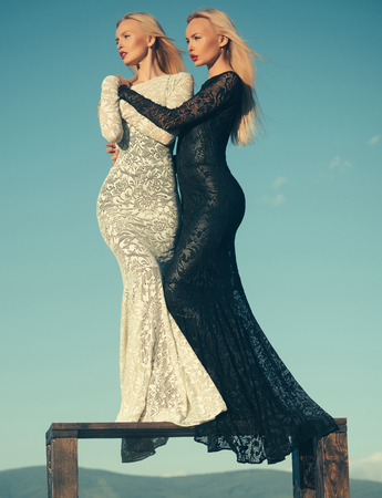 Fashion and beauty. Women wearing black and white dresses. Two girls with long blond hair posing on blue sky. Opposites and contrasts concept. Choice, decision and future. Stok Fotoğraf