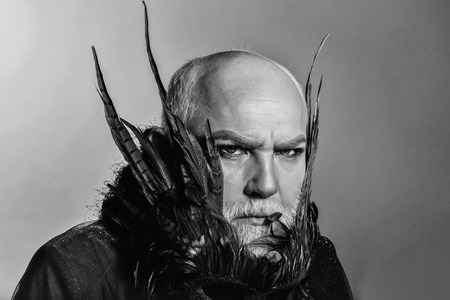 Male face with green eyes white beard gloomy frown sight hairless with theatre mask with dark feathers on his neck in black cloth on gray background studio Stock fotó