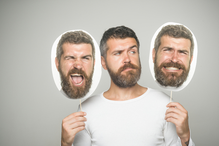 Hipster with winking and serious face hold portrait nameplate. Man with long beard and mustache. Guy or bearded man on grey background. Feeling and emotions. Barber fashion and beauty. Banco de Imagens