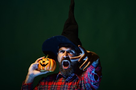 Halloween hipster with beard and jack o lantern. Man in wizard hat shouting with pumpkin on green background. Trick or treat. Autumn holiday celebration. Mystery and magic concept. Stock Photo