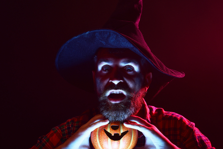 Halloween man in witch hat holding pumpkin in dark. Sorcerer with beard in red light. Magic illumination and jack o lantern. Autumn holiday celebration. Mystery and nightmare concept.