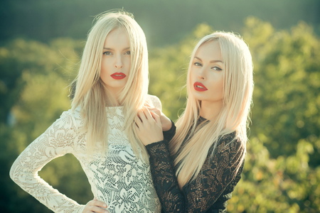 Contrasts and opposites concept. Dualism and dualistic nature. Beauty and fashion. Sisters twins posing on natural landscape. Two women with red lips and long blond hair. Stock Photo
