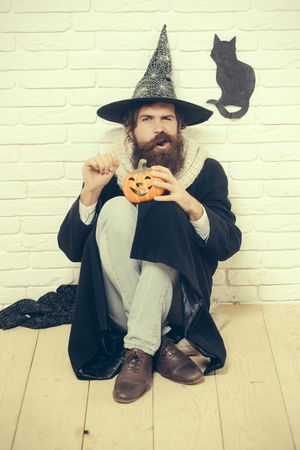 Celebração de feriados de outono de Halloween. Hipster com símbolo de abóbora e gato preto na parede. Mau feitiço e magia. Conceito de má sorte. Homem que torce a boca no chapéu da bruxa que senta-se no assoalho. Foto de archivo - 87558669