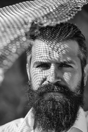 handsome young man with long beard and moustache on serious face with metallic net sunny day outdoor Zdjęcie Seryjne