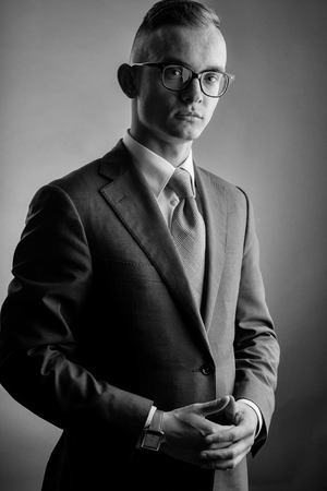 young fashion businessman with nerd glasses and stylish hairdo in jacket posing on grey background