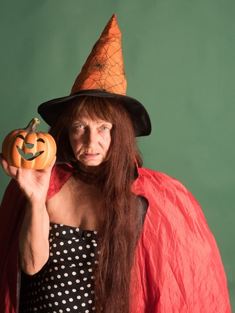 Halloween woman holding pumpkin on green background. Senior lady with long red hair in witch hat. Evil spell and magic. Trick or treat. Holiday celebration concept.