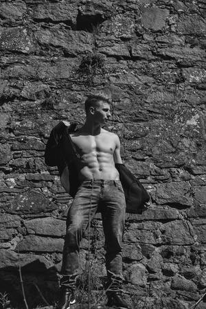 男の裸胸若いポーズ ジーンズ壁画の背景に屋外でのセクシーなモデル