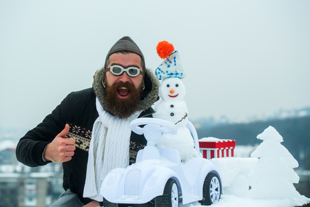 Bearded hipster in pilot hat and glasses showing thumbs up. Excited man on winter landscape. Snowman driving toy car on white sky. Christmas and new year. Holidays celebration concept.