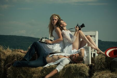 cute guy: Brunette woman with camera. Friends relaxing on sunny day on blue sky. Blond girl with vintage typewriter. Man or macho lying on hay. Summer vacation concept.