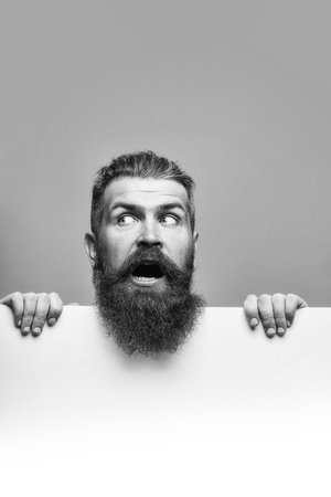 handsome bearded man with long lush beard and moustache on scared face with white paper sheet in studio on grey background, copy space